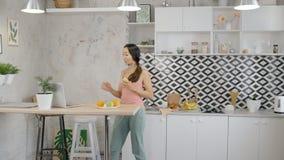 El ama de casa joven está comiendo la manzana, usando el ordenador portátil que se coloca en la cocina casera metrajes