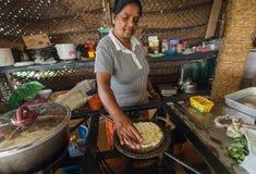 El ama de casa mayor que cocina roti tradicional del pan y la otra comida en el pueblo contienen la cocina imágenes de archivo libres de regalías