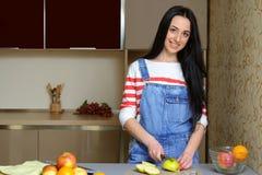 El ama de casa morena en guardapolvos azules corta una manzana en la cocina Imagenes de archivo