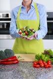El ama de casa muestra las verduras tajadas foto de archivo