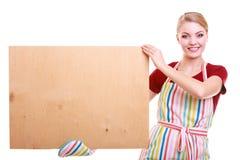 El ama de casa o el barista en delantal de la cocina lleva a cabo la muestra en blanco vacía del tablero aislada Fotografía de archivo