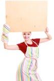 El ama de casa o el barista en delantal de la cocina lleva a cabo la muestra en blanco vacía del tablero aislada Imagen de archivo