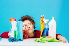 El ama de casa parece cansada y profunda en pensamientos mientras que limpia y lávase Imagen de archivo