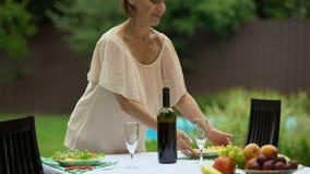 El ama de casa perfecta fija la tabla con la comida sana, preparación para la celebración metrajes