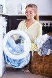 El ama de casa que toma la ropa hacia fuera trabaja a máquina Imagen de archivo