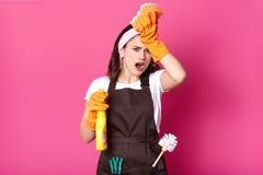 El ama de casa de sexo femenino chocada que lleva a cabo esponjas y el espray detergente en manos, lleva el delantal, siendo en p fotos de archivo libres de regalías