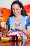 El ama de casa sonriente con una tostada en su mano y poner alguno atascan en ella Diversos potes con diversos sabores Foto de archivo