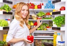 El ama de casa toma la pimienta roja del refrigerador Imágenes de archivo libres de regalías