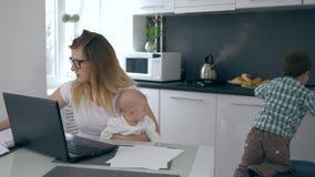 El ama de casa de trabajo con los niños, madre del negocio regaña al hijo que interfiere con el trabajo en casa almacen de metraje de vídeo