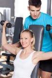 El amaestrador que ayuda a una mujer se resuelve con pesas de gimnasia Imagen de archivo libre de regalías