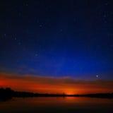 El amanecer de la mañana en un cielo estrellado del fondo reflejó en el agua Fotografía de archivo libre de regalías