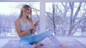El amante de la música en auriculares escucha las melodías y las danzas que se sientan cerca de ventana en casa almacen de video