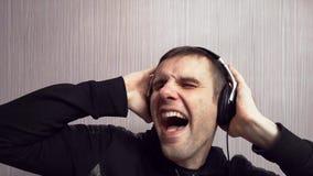 El amante de la música joven escucha la música en auriculares con emociones y gritos expresivos Concepto creativo de la música metrajes