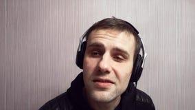 El amante de la música joven escucha la música en auriculares mientras que trabaja, presentando en ropa negra Concepto creativo d almacen de metraje de vídeo