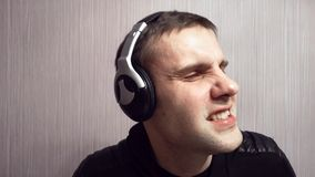 El amante de la música joven escucha la música en auriculares mientras que trabaja y goza el presentar en ropa negra Música creat almacen de video