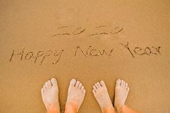 El amante escribe 2020 Felices Año Nuevo en la playa Foto de archivo