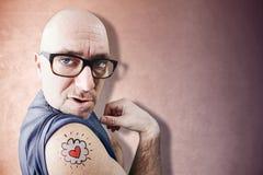 El amante latino divertido muestra su tatuaje Imagen de archivo