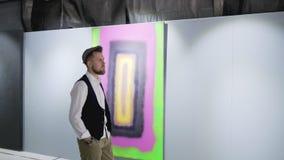 El amante masculino del arte está dando un paseo en el pasillo de la galería de arte y de imágenes de visión metrajes