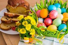 El amarillo agradable de la primavera florece, los huevos de Pascua y torta tradicional del día de fiesta Imagenes de archivo