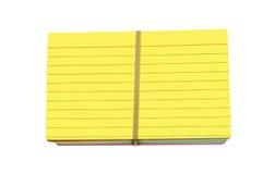 El amarillo brillante coloreó tarjetas de índice de la pila envueltas con la goma Foto de archivo libre de regalías