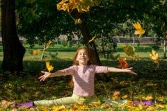 El amarillo del tiro de la muchacha se va para arriba en otoño en el parque Fotografía de archivo libre de regalías