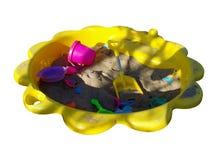 El amarillo embroma la salvadera con los juguetes aislados en blanco Fotografía de archivo libre de regalías
