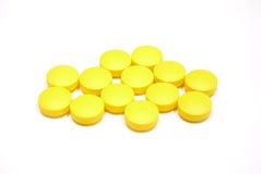 El amarillo hace tabletas píldoras en el fondo blanco Imágenes de archivo libres de regalías