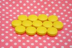 El amarillo hace tabletas píldoras en fondo rosado Imágenes de archivo libres de regalías