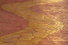 El amarillo tejó la calzada con las tejas anaranjadas Imagenes de archivo