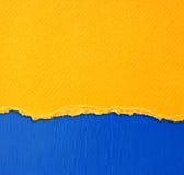 El amarillo texturizó el papel rasgado sobre fondo azul de la pared foto de archivo libre de regalías