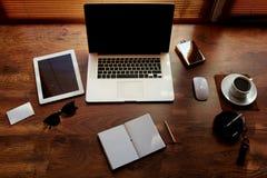 El ambiente del trabajo doméstico en una tabla de madera es un ordenador portátil, una taza de té, sobre blanco Fotos de archivo