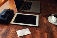 El ambiente del trabajo doméstico en una tabla de madera es un ordenador portátil, una taza de té, sobre blanco, vidrios Fotos de archivo