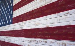 El americano o Estados Unidos señala por medio de una bandera pintado en una pared de madera del tablón Imagenes de archivo
