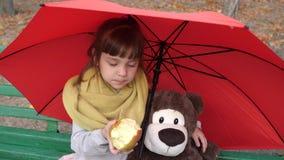 El amigo de la niña y del juguete se sienta en un banco en parque debajo de un paraguas y come la manzana roja almacen de video