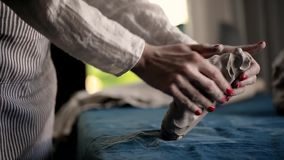El amo amasa el terrón de la arcilla en una lona azul Arcilla de modelado, hecha a mano almacen de video