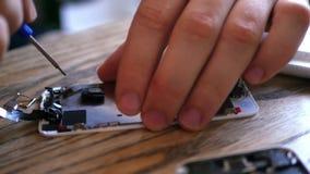 El amo analiza el teléfono quebrado, saca de él los pequeños detalles con un destornillador especial 4K 30fps almacen de video