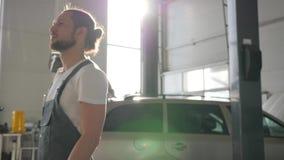El amo auto del retrato habla en el teléfono móvil en la gasolinera, mecánico de la máquina en smartphone de los controles del co metrajes