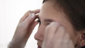 El amo corrige las cejas en un salón de belleza, midiendo la forma perfecta para la cara de los clientes Cuidado profesional para almacen de video