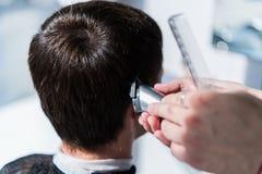 El amo corta el pelo de los hombres en la barbería, peluquero hace el peinado para un hombre joven imagen de archivo