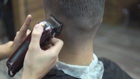 El amo corta el pelo y la barba de los hombres en la barbería, peluquero hace el peinado para un hombre almacen de video