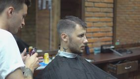 El amo corta el pelo y la barba de los hombres en la barbería, peluquero hace el peinado para un hombre joven metrajes