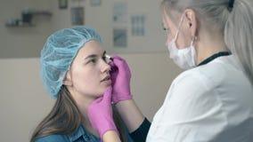 El amo de la frente aplica la pintura en cara de la mujer en clínica de la belleza metrajes