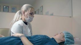El amo de la frente consulta a la muchacha en las cejas que tatúan en salón almacen de metraje de vídeo