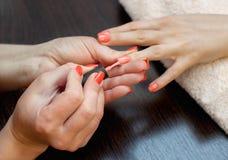 El amo de la manicura pinta clavos con el esmalte de uñas durante el procedimiento de las extensiones del clavo con el gel en el  Fotografía de archivo libre de regalías