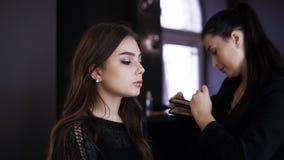 El amo del maquillaje aumenta las pestañas, compone al artista que hace los latigazos largos, mujer en estudio de la belleza hace almacen de video