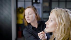 El amo del maquillaje está aplicando el polvo en piel de la cara de la mujer rubia hermosa del cliente en tienda de belleza almacen de metraje de vídeo