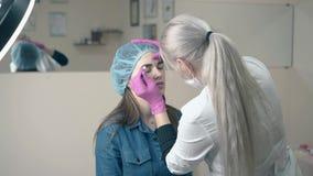El amo del maquillaje hace la ceja que tatúa al cliente en salón almacen de video