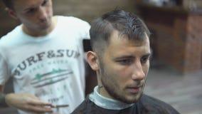 El amo del primer corta el pelo y la barba de los hombres en la barbería, peluquero hace el peinado para un hombre joven almacen de metraje de vídeo