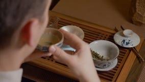 El amo del té vierte la infusión de la taza de la imparcialidad en el cuenco y bebe té chino almacen de metraje de vídeo