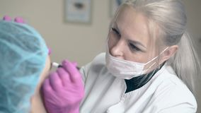 El amo en máscara hace las frentes que tatúan en cara de la mujer en clínica almacen de video